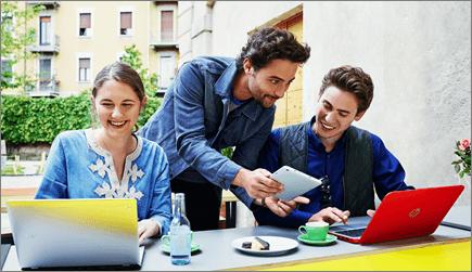 Foto av tre personer som arbetar på bärbara datorer.
