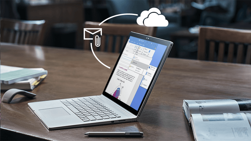 รูปภาพของแล็ปท็อปบนโต๊ะที่มีสิ่งที่แนบมาและสัญลักษณ์ OneDrive