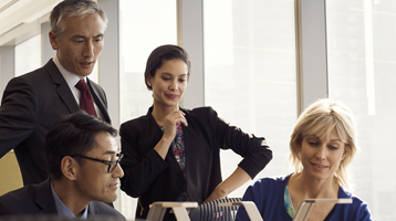 Yüksek kattaki bir ofiste yer alan ufak bir konferans odasında toplanan bir ekibi gösterir.