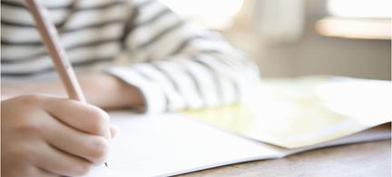 Elinde kitap ve kalem olan bir çocuk
