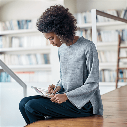Surface tablet bilgisayarda çalışan bir kadının fotoğrafı.