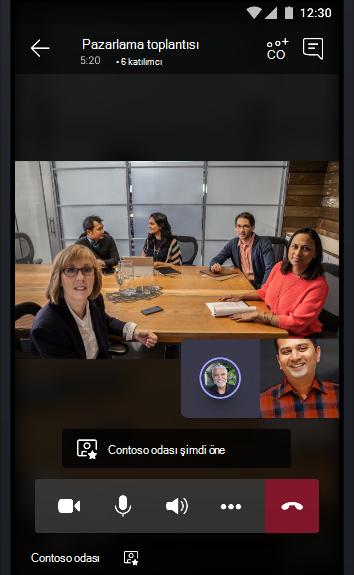 Diğer iki toplantı katılımcısıyla konuşan insanlarla dolu bir konferans odasının teams çevrimiçi toplantısına ait görüntü.