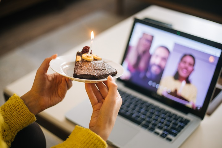photo of a person holding a pice of cake up in of a web cam