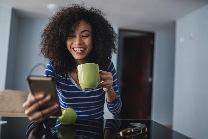фотографія жінки, яка дивиться на її телефон.