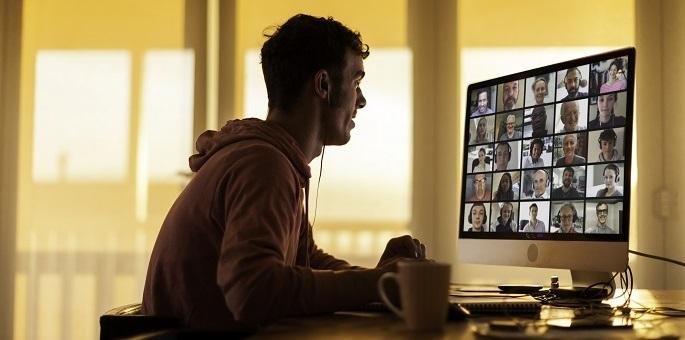 фотографія чоловіка за комп'ютером із відеонарадою на екрані