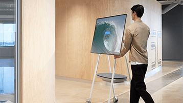 Чоловік пересуває пристрій Surface Hub