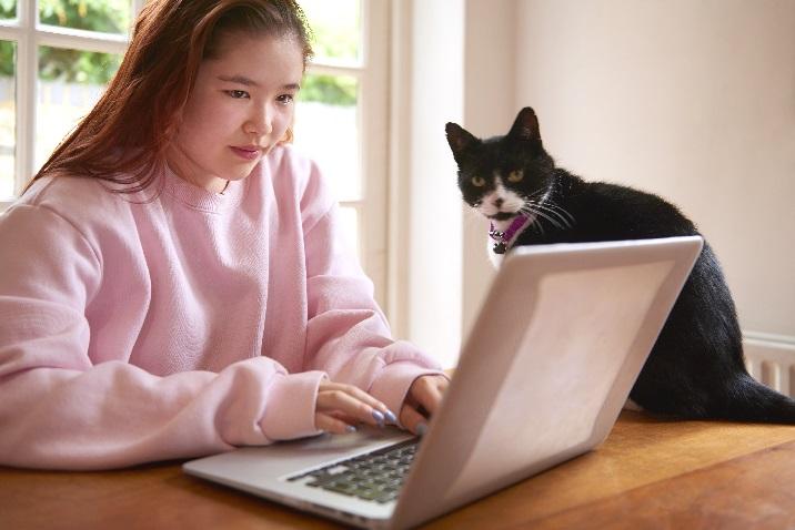 фотографія жінки на ноутбуці з її кітом.