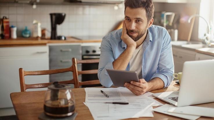 hình ảnh một người đàn ông đang ngồi tại bàn trong nhà bếp, bên máy tính và lập kế hoạch cho một ngày của bản thân