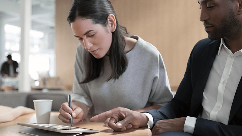 一名女士和一名男士一起在 Surface 平板电脑上工作。