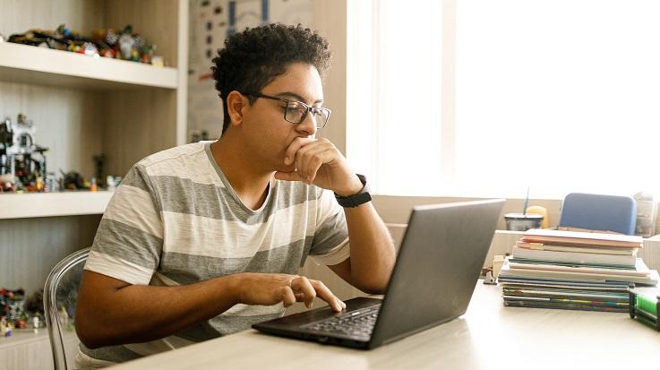 一名学生在笔记本电脑上工作的照片