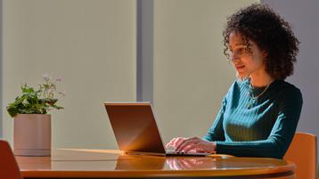 一位坐在办公桌前、携带笔记本电脑的女士