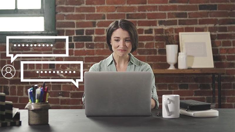 一个女人坐在笔记本电脑前,电脑上有聊天气泡