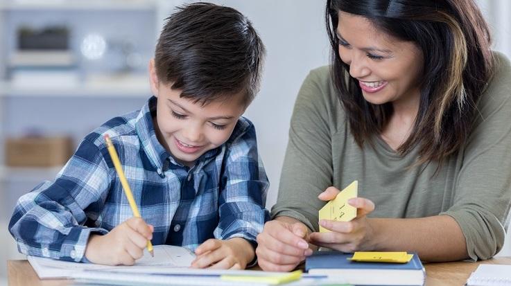 成人辅导孩子完成家庭作业的照片。