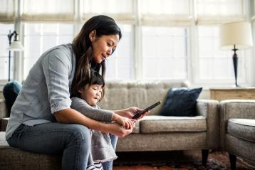 一位母親和她的小女兒正在看著母親的電話
