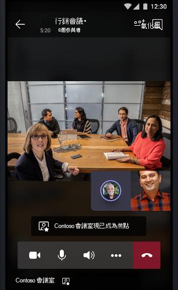 一個 Teams 與一間充滿了人的會議室進行線上會議,且正與其他兩位會議參與者談話的圖片。